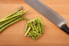 Chopped fresh raw asparagus. On wooden background Royalty Free Stock Photo