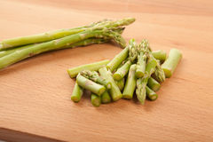 Chopped fresh raw asparagus. On wooden background Stock Photo