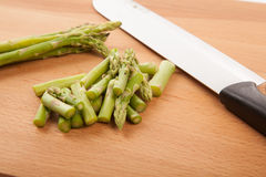 Chopped fresh raw asparagus. On wooden background Royalty Free Stock Photography