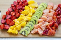 Chopped fresh raw colorful fruits arranged on cutting board on w. Hite wooden background, closeup Stock Photo