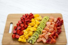 Chopped fresh raw colorful fruits arranged on cutting board on white wooden background, closeup. Copy space Stock Photography