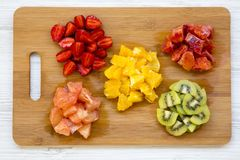Chopped fresh raw colorful fruits arranged on cutting board on white wooden background, top view. Flat lay royalty free stock images