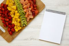 Chopped fresh raw fruits arranged on cutting board and notebook on white wooden table, top view. From above, flat lay,. Overhead stock image