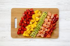 Chopped fresh raw fruits arranged on cutting board on white wooden table, top view. From above,. Flat lay, overhead stock photo