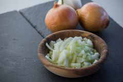 Chopped fresh and raw white onion slices in wooden bowl with bulbs. Close up Stock Images
