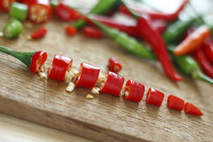 Chopped fresh red and green chilli on wooden chopping block. Stock Photos