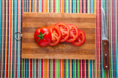 Sliced tomatoes on board. Chopped fresh tomatoes on a kitchen board Royalty Free Stock Images