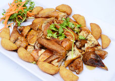 Chopped fried chicken with potatoes and herbs on white platter Royalty Free Stock Photo