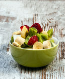 Chopped fruit. In a bowl surrounded by rustic background Royalty Free Stock Photos