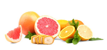 Chopped fruits over the white background. Colorful grapefruit, lemon, oranges. Fresh mint leaves and slices of a banana. stock photography