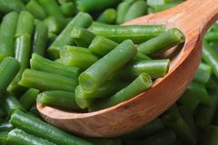 Chopped green beans closeup on wooden spoon. Background. Macro Stock Photos