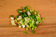 Chopped green onion on woode board. Top view Stock Images