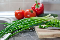 Chopped green onions and vegetables on striped wooden board Stock Image