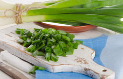 Chopped green onions on a white wooden cutting board. Stock Image
