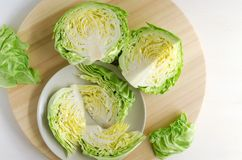 Chopped head of cabbage. Fresh green chopped and sliced head of cabbage on wood cutting board, prepared for salad. Homemade cooking concept Royalty Free Stock Photo
