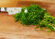 Chopped herbs on cutting board. With a knife Stock Photography