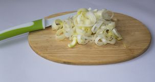 Chopped leek on a cutting board and knife. 