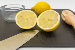 Chopped Lemon on Board with Knife. A display of a Chopping Board with Lemons and Knife Stock Images