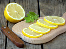 Chopped lemon slices on wooden board, knife and sprig of mint Stock Photos