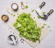 Chopped lettuce with knife for herbs, Mortar Pepper on a cutting board with oil wooden rustic background top view close up Royalty Free Stock Image
