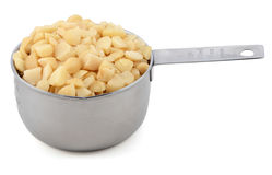 Chopped macadamia nuts in a cup measure Stock Images