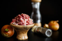 Chopped meat in a wooden bowl with spices. On a black background Royalty Free Stock Images