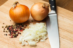 Chopped Onion on Wooden Cutting Board with Knife and Pepper Stock Image