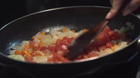 Chopped onions, carrot and tomato fried in vegetable oil in the pan. Close-up adding tomato on top of the pan. stock video footage