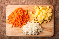 Chopped onions, carrots, potatoes stacked in groups on a wooden Stock Photography