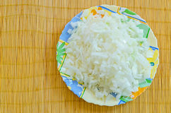Chopped onions on colorful plate on a bamboo mat. Chopped onions on a plate prepared for further cooking Royalty Free Stock Image
