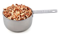 Chopped pecan nuts in a metal cup measure Stock Image