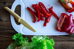 Chopped pepper on the tip with knife and salad royalty free stock images
