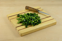 Chopped poblano pepper. On wooden cutting board with knife royalty free stock images
