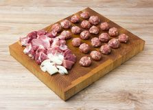 Raw meatballs on the board. Chopped pork meat and chopped onions next to the meatballs Royalty Free Stock Images