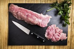 Chopped pork sirloin next to a knife and a few branches of parsley on a black slate griddle. Chopped pork tenderloin next to a knife and some branches of parsley royalty free stock images