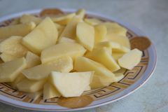 Chopped potatoes. In the chopped potato plate . Sliced, peeled raw potatoes on a board . Chopped potatoes in a bowl . Diced potato stock image