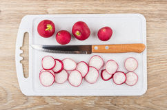 Chopped radishes and kitchen knife on plastic cutting board. On wooden table. Top view Royalty Free Stock Photography