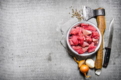 Chopped raw meat with an axe, cutting knife and spices. On the stone table. Free space for text . Top view Royalty Free Stock Images