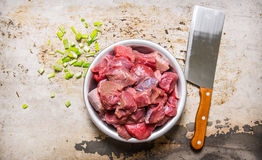 Chopped raw meat in a bowl with green onion and a knife for cutting meat. On rustic background. Top view Royalty Free Stock Photo