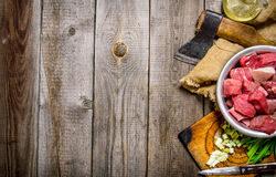 Chopped raw meat. With fresh onions and an axe on an old fabric. On a wooden table.  Free space for text . Top view Royalty Free Stock Photo