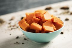Chopped raw pumpkin in a bowl. Closeup of a pile of chopped raw pumpkin in a pale green bowl placed on a wooden table stock image