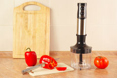 Chopped red bellpepper with tomato and a blender on kitchen table Royalty Free Stock Photo