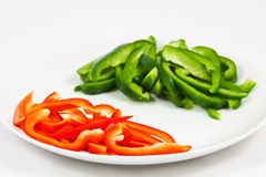 Chopped red and green peppers on white Stock Images