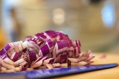 Chopped Red Onion Pile. Pile of chopped red onion next to a blue knife royalty free stock photos