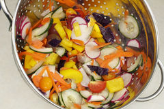 Chopped Salad Vegetables Mix in a Colander. Colorful vegetables variety of red radishes, cucumbers, yellow sweet bell peppers, carrots, cabbage, red and orange Stock Photography