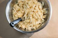 Chopped skalade päron och en kniv i en metallbunke arkivbilder