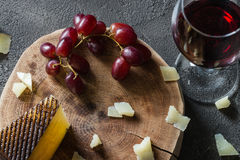 Chopped Spanish hard cheese manchego on wooden cut with red grapes and a glass of red wine. On dark rustic background, top view Royalty Free Stock Image