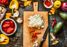 Chopped spices on wooden cutting board with knife: chili, onion and garlic with vegetables ingredients for Mexican cuisine on dar Stock Photos