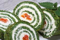 Chopped spinach roulade with cream cheese macro. Chopped spinach roulade with cream cheese on a white plate macro horizontal Royalty Free Stock Images