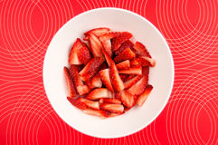 Chopped strawberries in a bowl against a patterned background Royalty Free Stock Photography
